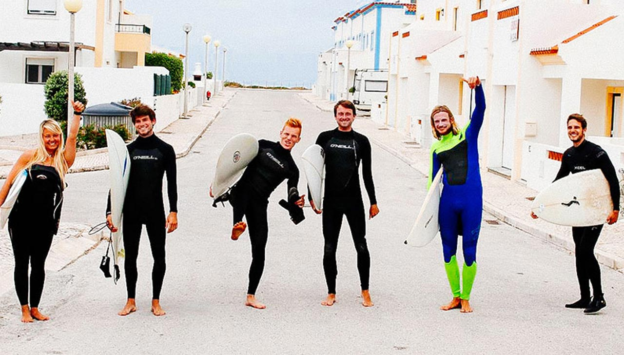 Crew of surfers in wetsuits carrying surboards ready for a surf in Baleal, Lagide in Portugal